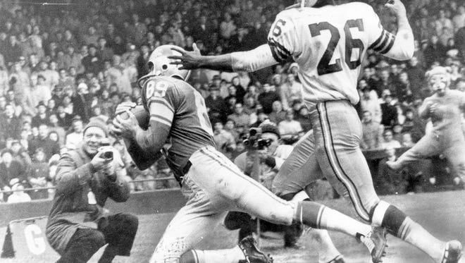 Gail Cogdill of the Detroit Lions catches a 27-yard touchdown pass from quarterback Milt Plum in front of Green Bay Packers cornerback Herb Adderly on Thanksgiving Day in 1962 in Detroit.