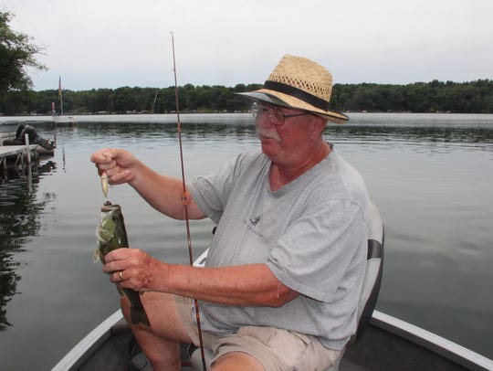 Mike Yurk of Hudson, Wis. unhooks a largemouth bass