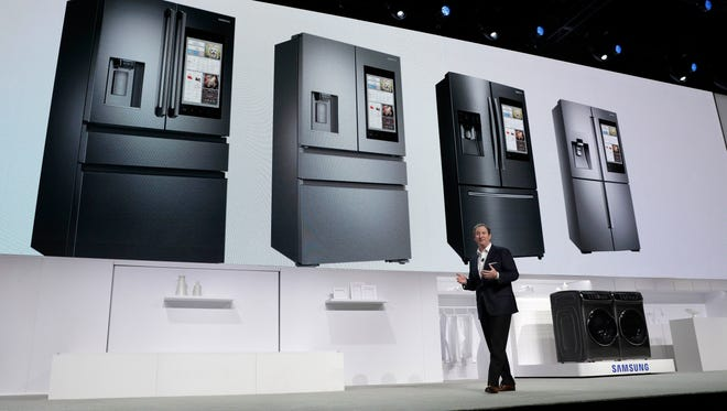 John Herrington, senior vice president of Samsung Electronics America, unveils new refrigerators with Family Hub 2.0 during a Samsung news conference before CES International on Wednesday in Las Vegas. Family Hub 2.0 features an interface on the refrigerator with apps that can be controlled by voice recognition.