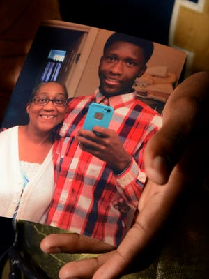Roberson High quarterback Darrion Payne cradles a photo of him and his mother Shirley.