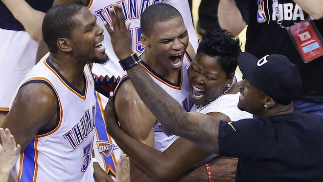 Kevin Durant and Russell Westbrook celebrate a Thunder win with Durant's mother, Wanda Pratt.