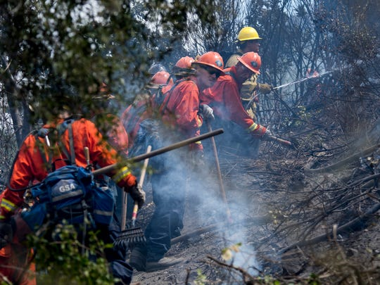 A San Bernardino County inmate hand crew works its way through brush to contain a fire in the Cajon Pass near Devore, Calif., on July 5, 2017.