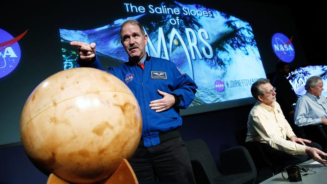 John Grunsfeld, associate administrator at NASA's Science Mission Directorate, speaks with colleagues at a news conference about Mars on Sept. 28, 2015, in Washington, D.C.