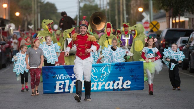 Ryan Ward, center, leads the annual Elf Parade through the streets of downtown Pensacola Friday night. The annual parade marks the official beginning of Winterfest along with the lighting of the downtown Christmas lights.