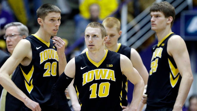 Iowa guard Mike Gesell (10), forward Jarrod Uthoff (20), forward Aaron White (30), and center Adam Woodbury (34) react during the second half of an NCAA college basketball game against Northwestern on Sunday, Feb. 15, 2015, in Evanston, Ill. Northwestern won in overtime 66-61. (AP Photo/Nam Y. Huh)