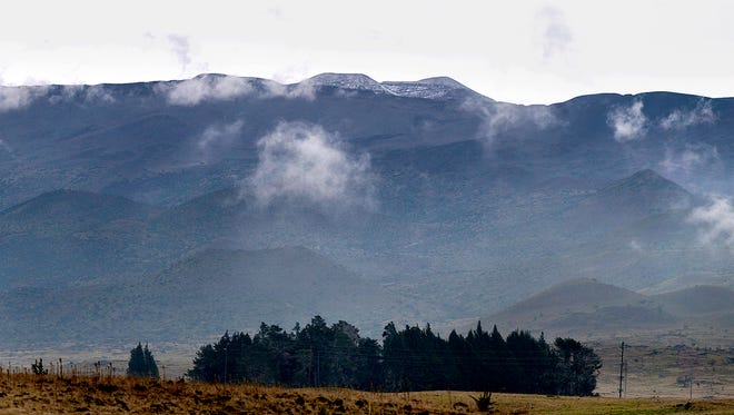 This Tuesday, Dec. 23, 2014 photo shows a dusting of snow on Mauna Kea on the Big Island of Hawaii. While snow on the mountains is common, a blizzard with significant accumulation is unusual.