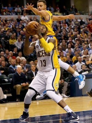 Indiana Pacers forward Paul George (13) gets Golden State Warriors guard Stephen Curry (30) in the air on a shot fake at Bankers Life Fieldhouse on Dec. 7, 2015.