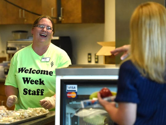 Ivy Tech employee Christina Rhan (left) chats with Alisha Aman while providing free breakfast for students and employees during the first day of classes at Ivy Tech Community College Southwest in Evansville Tuesday.