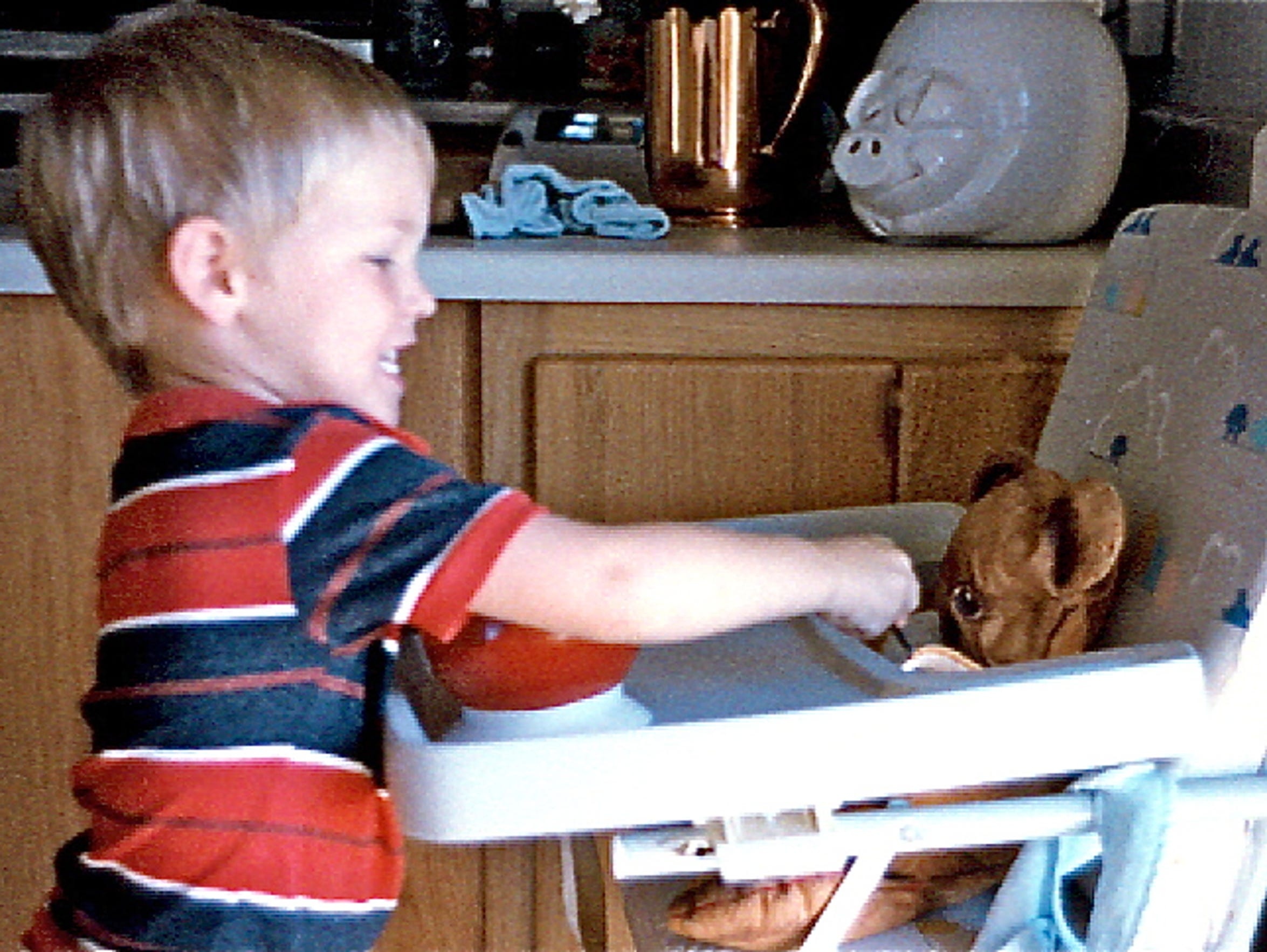 Sandy Swenson's son, Joey, feeds a stuffed bear as