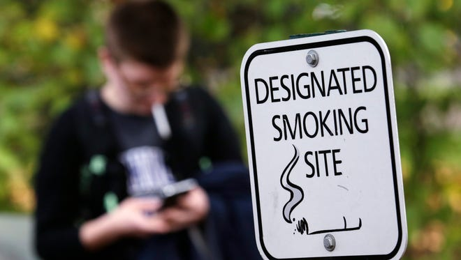 A University of Washington student smokes at one of a handful of designated smoking locations on the campus on Oct. 27, 2015, in Seattle.