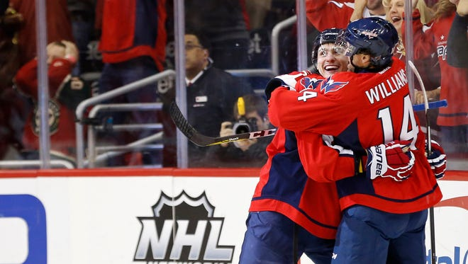 Washington Capitals defenseman Dmitry Orlov (9) celebrates with Capitals right wing Justin Williams (14) after scoring the go-ahead goal against the Minnesota Wild in the third period at Verizon Center.