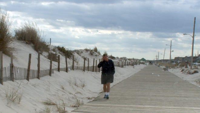 A man walks past the dunes that line the Seaside Park boardwalk last month. A man walks past the dunes that line the Seaside Park boardwalk Wednesday, October 14, 2015.