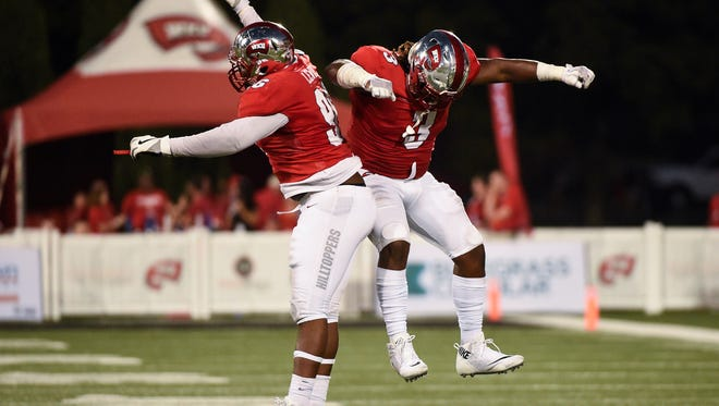 Western Kentucky defensive linemen Jaylon George (left) and Chris Johnson celebrate after a play during a game against Charlotte on Oct. 14 in Bowling Green, Kentucky.