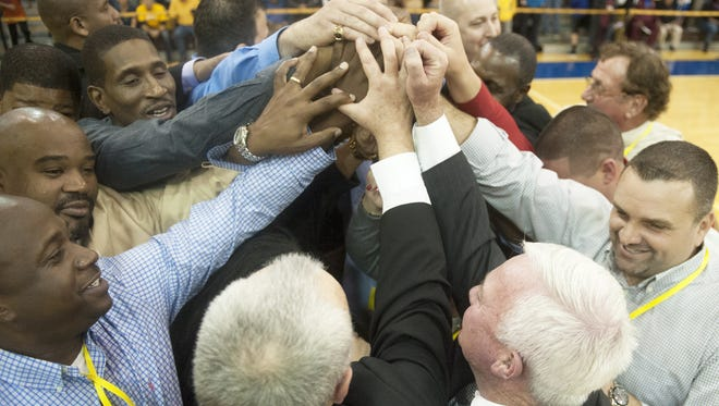 Members of Rowan's 1996 national championship team huddle together during Saturday's reunion.