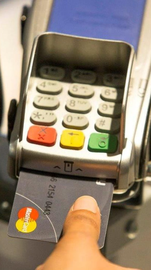 A person uses a thumbprint to make a purchase with