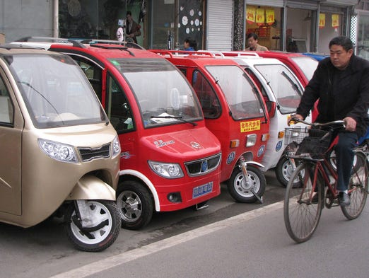 A man bikes past electric vehicles at a Green Source shop on Nov. 7 in eastern Beijing. The tiny three and four-wheelers form part of an illegal, growing and sometimes bizarre-looking fleet of electric-powered minicars bought by drivers desperate to bypass the traffic gridlock plaguing Chinese cities.