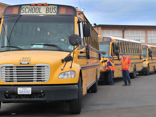 School buses wait outside Barwise Middle School to transport students home Thursday afternoon.
