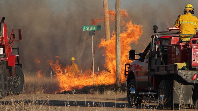 Reno County firefighters stand ready as they light a backfire to contain a grass fire four miles south and one mile east of Turon. Two dozen units, including trucks from the Preston Fire District, attacked the two-mile-long fire that burned CRP grass, CRP hay bales and trees the afternoon of March 6.