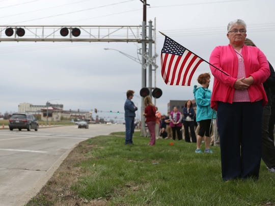 Bonnie Gilchrist, of Urbandale waits at the intersection of Ashworth Road and Jordan Creek Parkway to watch Des Moines Police Officer Susan Farrell's funeral procession on Wednesday, March 30, 2016, in West Des Moines.