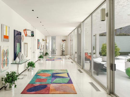 The house's entryway features a bright array of art and clerestory windows, which lead to an enclosed pool courtyard.
