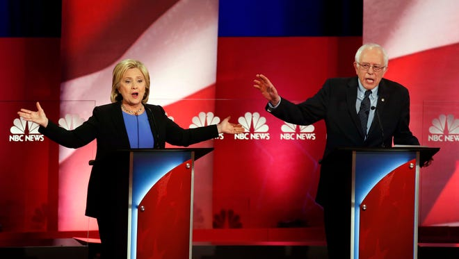 Democratic presidential candidates, former Secretary of State Hillary Clinton, left, and Sen. Bernie Sanders, I-Vt. talk over each other during the Democratic presidential primary debate at the Gaillard Center, Sunday, Jan. 17, 2016, in Charleston, S.C.