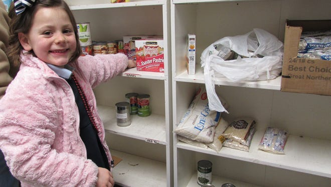 Ella Arnett helps to stock the shelves at the local food pantry.