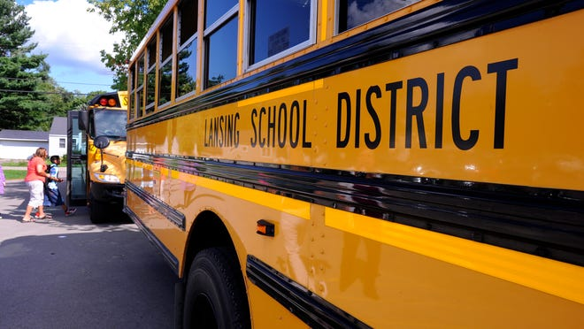 Schoolchildren get on buses at Lansing Sheridan Road STEM Magnet school in Lansing in September of 2014