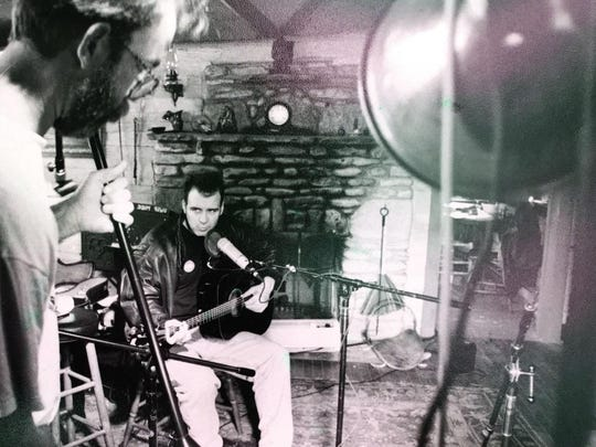 """Dave Alley, foreground, sets up in his studio to record his younger brother, Fred Alley. A tribute album of songs by the late Fred Alley, """"Solid Ground,"""" is being released at an Aug. 23 concert at Door Community Auditorium, with proceeds going to Northern Sky Theater's Constellation Campaign."""