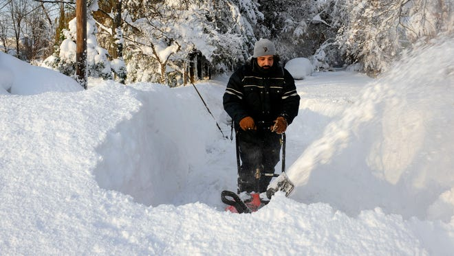 Bob Wilcox clears the snow at the end of his driveway on Nov. 19 on Bowen Road in Lancaster,  N.Y.