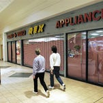 A couple of Forest Mall walkers stride past the closed Rex store recently.