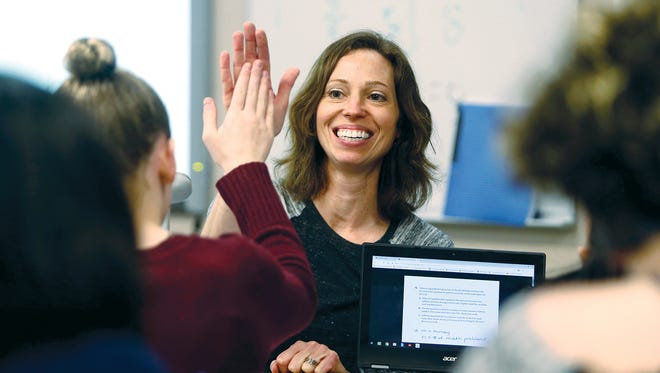 Woodward Middle School teacher Wendy Kozina high fives a student as she helps with math answers in her class.
