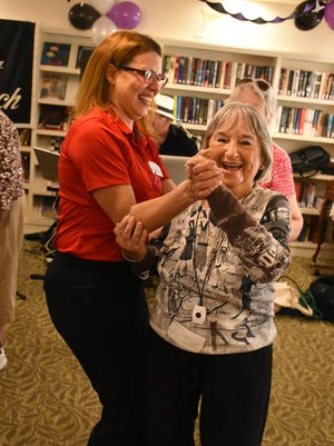 """Staffer Tania Gomez dances with a resident. Once a month, the """"Velvet Touch"""" duo brings their music to residents in the Inn at Aston Gardens."""