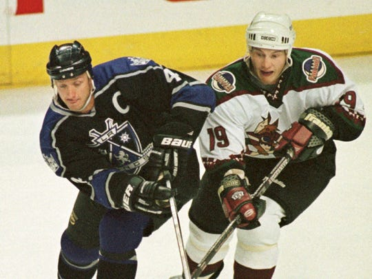 Los Angeles Kings captain Bob Blake, left, and Phoenix Coyotes' Shane Doan battle for control of the puck during the first period of their game at America West Arena in Phoenix Saturday Sept. 26, 1998.