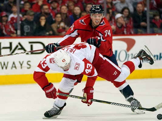 Washington Capitals defenseman John Carlson (74) and Detroit Red Wings left wing Darren Helm (43) chase the puck during the second period of an NHL hockey game Sunday, Feb. 11, 2018, in Washington. (AP Photo/Pablo Martinez Monsivais)