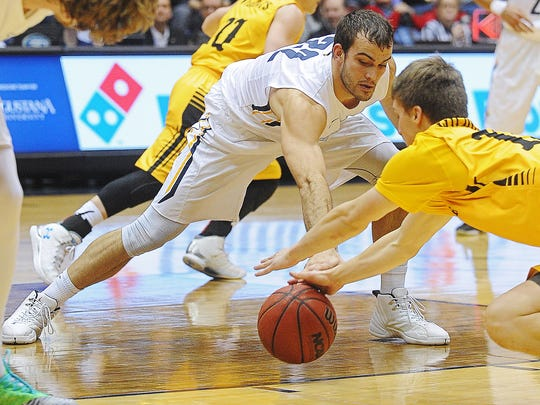 Wayne State's Brian Goodwin (15) dives on a loose ball as Augustana's Casey Schilling (32) attempts to grab it during a game Saturday at the Sioux Falls arena.