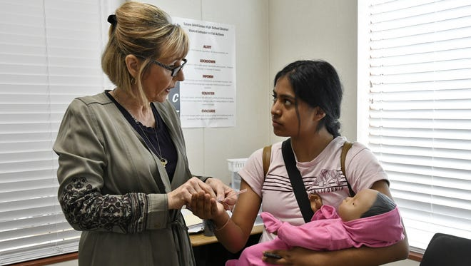 Mission Oak High School teacher Laurie Hollman helps student Citali Palafox, 18, put on her baby-tracking bracelet Friday morning.