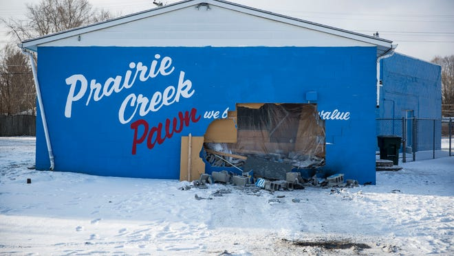 A large hole made by a vehicle is all that remains of an overnight burglary at Prairie Creek Pawn at Burlington Drive and Macedonia Avenue, on Feb. 6, 2018. One of the suspects in the burglary was hospitalized after suffering a cut during the burglary.