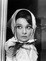 "Audrey Hepburn runs for cover in the 1964 comedy ""Charade."""