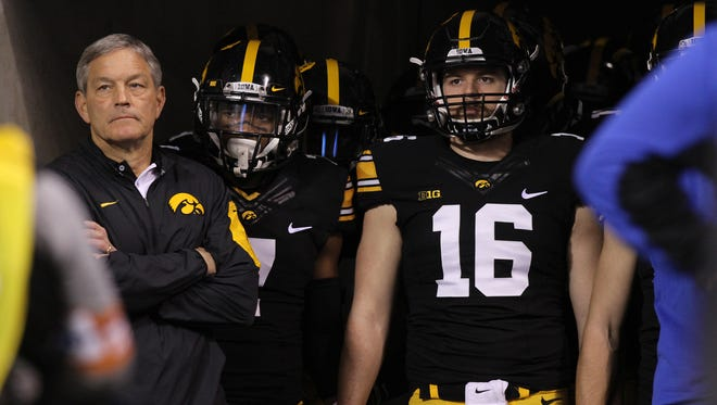 Iowa head coach Kirk Ferentz and punter Dillon Kidd wait to take the field for the Hawkeyes' Big Ten championship game against Michigan State at Lucas Oil Stadium in Indianapolis on Saturday.