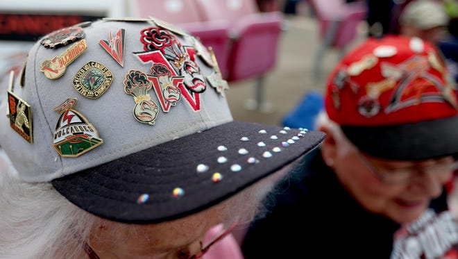 Friends Kay Taylor, of Keizer, left, and Jan McAneny, of Salem, wear caps with pins from every season before the 20th anniversary season opener for Volcanoes baseball at Volcanoes Stadium in Keizer on Friday, June 17, 2016.