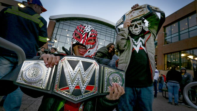 WWE Smackdown fans wait in line to get in and see the live wrestling event Tuesday, March 4, 2017, evening at Bankers Life Fieldhouse. Rilen Stewart and his brother Riley,right, hold their wrestling belts high before the main WWE event in the Fieldhouse.