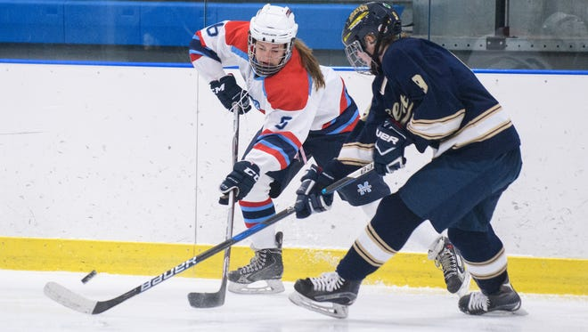 CVU-MMU's Caroline Reynolds (5) battles for the puck with Essex's Olivia Miller-Johnson (9) during the girls hockey game between the Essex Hornets and the CVU-MMU Cougarhawks at the Essex Skating Facility on Wednesday night December 13, 2017 in Essex.