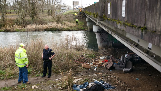 Salem Police Officer Bob Owings and state officials stand near a homeless camp under the Highway 22 overpass that crosses Mill Creek near Costco and Lowe's on Monday, Jan. 29, 2018. The Oregon Department of Transportation cleared the camp on Monday, after posting temporary signs on Jan. 16 warning people to remove their property.