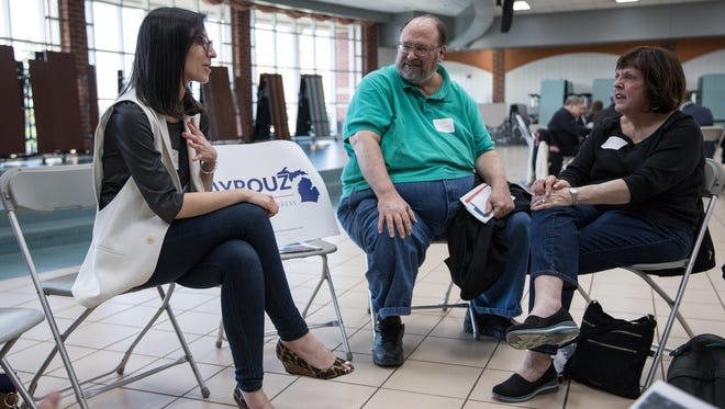 "11th Congressional District candidate Fayrouz Saad, left, talks to voters including Joseph McCauley of Northville, center, during a ""candidate speed dating"" event hosted by the Northville Democratic Club and Fems for Dems at Northville High School in Northville, Thursday, April 26, 2018."