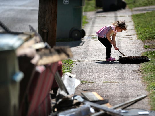 Adalyn Morano, 3, messes with a neighborhood cat Wednesday morning on Townes Street as extra trash, including a discarded couch, litters the curb after the family's spring cleaning. The city is exploring four options for picking up curbside trash not in carts, nearly all of which would mean higher fees for residents.