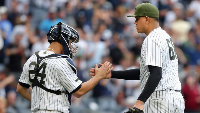 Yankees catcher Gary Sanchez (24) celebrates with relief pitcher Dellin Betances (68) after defeating the Oakland Athletics at Yankee Stadium on Saturday, May 27, 2017.