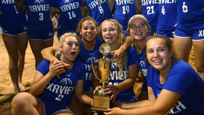 Xavier Prep celebrates with their trophy after defeating Millennium high to win the Div. I beach volleyball high school state final on Tuesday, May 2, 2017 at Mesquite High School in Gilbert, Ariz.