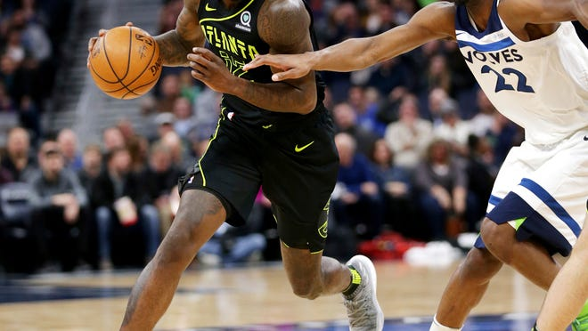 Atlanta Hawks forward Taurean Prince (12) drives on Minnesota Timberwolves forward Andrew Wiggins (22) during the first quarter of an NBA basketball game Wednesday, March 28, 2018, in Minneapolis. (AP Photo/Andy Clayton-King)