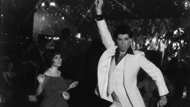 "John Travolta and Karen Gorney dance in a nightclub scene to disco music in Paramount Pictures 1977 film ""Saturday Night Fever"", which explores the restless generation growing up in the 70's."
