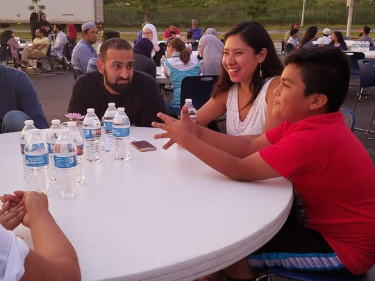 From left, Saad Faroog Azax, 28, Nancy Flores, 29, and Luis Flores, 9, participate in a table discussion